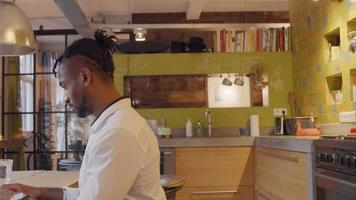mogen svart man sitter vid köksbordet och skriver på bärbar dator, kök på bakgrund video