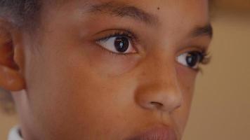 Close up of girl, eyes watching screen, she talks - screen not shown video