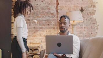 homem sentado com o laptop na frente dele fala, fazendo videochamada, a garota entra e empurra o homem, o homem observa a garota, empurra-a e tenta continuar a videochamada, enquanto a garota empurra e puxa o braço dele, o homem sorri