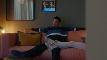 jovem asiático se senta no sofá, assiste televisão, se inclina para trás, pernas de mulher em sua perna