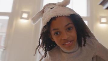 close-up de garota, correndo em círculos na sala de estar, moletom na cabeça video
