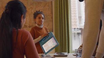 garota em frente à mesa, segura seu tablet, fala com duas mulheres e um homem à mesa. mulher desiste do polegar, fala, as pessoas riem, garota anda em volta da mesa, mostra tablet para mulher e homem