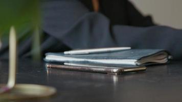 celular atendido na mesa onde jovem empresária negra assiste a tela e atende o telefone