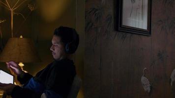 asiatischer junger Mann sitzt im Sessel, Kopfhörer an, hält Tablet, dreht es, rollt