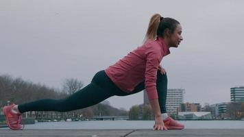 jovem negra no parque em uma plataforma de madeira, à beira-mar, fazendo exercícios físicos, estica uma perna inteiramente atrás dela, a outra perna dobrada na frente dela, dobrando o corpo para a frente