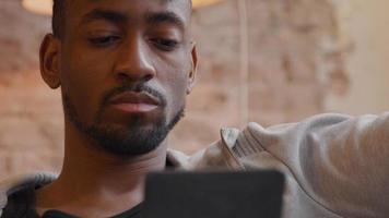 homem maduro lendo em um tablet colocado à sua frente video