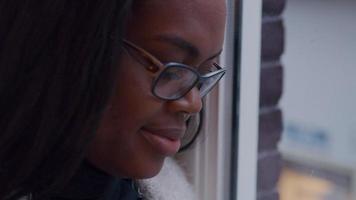 close-up de mulher ao lado da janela, cabeça voltada para o telefone móvel, digitando. video