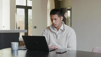Asian young man, sitting at table, watching laptop screen, talks and scrolls