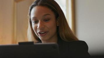zwarte jonge zakenvrouw zittend aan tafel met een video-oproep, luisteren en spontaan reageren video