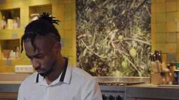 svart man sitter i köket, ögonen rör sig något upp och ner, huvudet svagt nedåt medan han arbetar på bärbar dator - laptop visas inte video