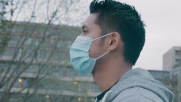 jovem asiático andando lá fora, usando máscara facial