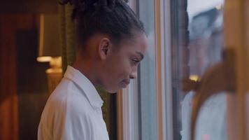 svart tjej tittar genom fönstret, pannan på fönstret video