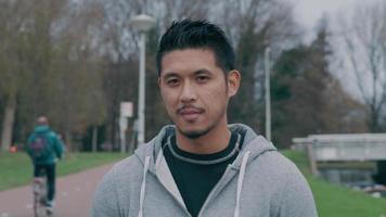 jovem asiático parado do lado de fora, olhando para a câmera, sorrindo levemente, piscando