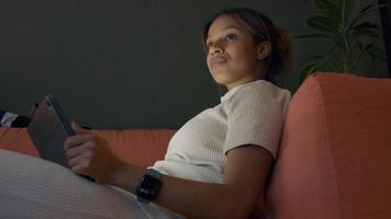 Joven negra sentada en el sofá, apoyado en el apoyabrazos, mirando la tableta, mira hacia arriba, mira la televisión