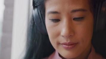 close-up de uma mulher madura, olhos olhando para baixo, fone de ouvido nas orelhas, movendo a cabeça suavemente video