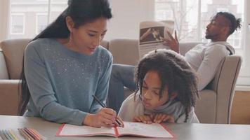 mulher e menina sentada no chão à mesa. livro e lápis de cor na frente deles. mulher fala, aponta com lápis no livro de trabalho. garota segue o lápis. homem no sofá no fundo, lê o jornal. video