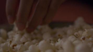 close-up de uma tigela de pipoca, dedos de uma jovem negra pegando pipoca video