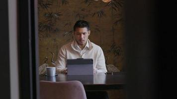 Asian Young man sitting at table with laptop, having conversation by video-call