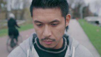 close-up van Aziatische jonge man die buiten, hoofd naar beneden, hoofd draait omhoog