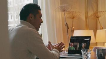 Asian young man having a video-call with women on laptop screen