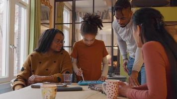 garota em frente à mesa, usando o tablet infantil com caneta stylus. duas mulheres, sentadas ao redor da mesa e o homem de pé, se inclina, todas assistindo ao tablet. mulheres falam.