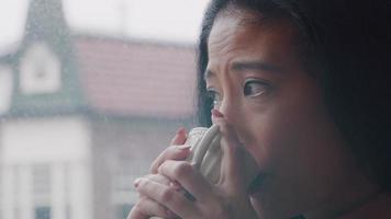 close-up de uma mulher madura, olhando pela janela contemplativamente, bebendo, com o copo em ambas as mãos video