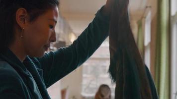 mulher ajusta a gola do casaco, enrola o lenço no pescoço, ajusta o cabelo e coloca uma máscara facial