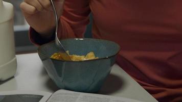 close-up da mão de uma jovem negra, misturando flocos de milho e leite em uma tigela com uma colher e dando uma mordida video