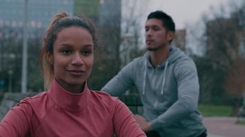 jovem asiático e uma jovem negra no parque, fazendo exercícios físicos, esticando a perna, corpos retos