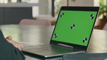 tela verde na tela do laptop, mãos de uma jovem negra em frente ao teclado-mousepad video