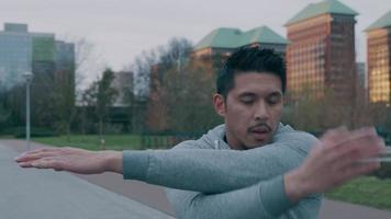 Aziatische jongeman in park, lichaamsbeweging doen, armen en vuisten voor hem kruisen