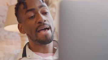 L'homme avec un ordinateur portable en face de lui parle vivement, hoche la tête et fait des gestes, tout en ayant un appel vidéo video