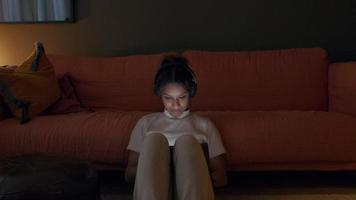 jovem negra na sala de estar, sentada no chão, encostada no sofá, com fone de ouvido, assistindo tablet