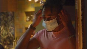 mannen framför spegeln, huvudet neråt, huvudet uppåt, sätter på ansiktsmasken och justerar den video