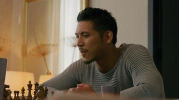 joven asiático se sienta a la mesa, jugando al ajedrez