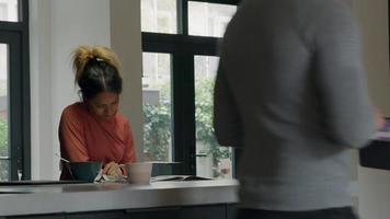 schwarze junge Frau liest Zeitung, sitzt am Küchentisch, asiatischer junger Mann schließt sich mit Tablette an