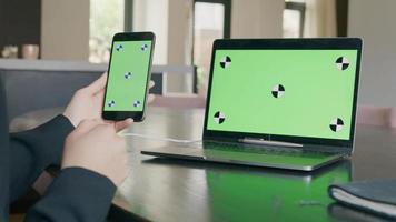 celular com tela verde na mão de mulher negra, laptop no fundo com tela verde