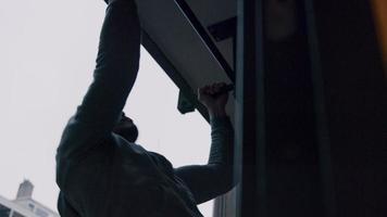 Joven asiático haciendo pull ups afuera, con asas en la barra, cerca de la pared, mirando hacia la pared video
