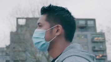 close-up de jovem asiático caminhando lá fora, usando máscara facial