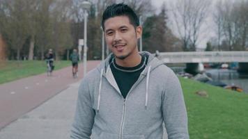 jovem asiático parado do lado de fora, olhando para a câmera, começa a sorrir