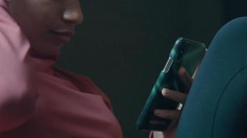 primer plano, de, negro, mujer joven, sentado, mirar, y, tocar su teléfono celular, poniendo, pelo, atrás, oreja