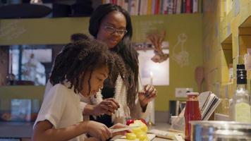 mujer y niña de pie junto a ella en la encimera de la cocina. mujer da cuchillo a niña, niña corta pimentón, mujer instruyéndola