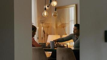 Joven negra y joven asiático sentado a la mesa jugando al ajedrez