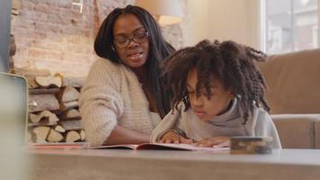 mujer y niña sentada en el suelo a la mesa. libro frente a la niña, la mujer y la niña hablan, la niña mira el libro. la mujer señala el libro, la niña comienza a leer, el dedo índice sigue las palabras.