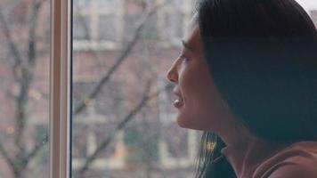 mujer madura sentada en el alféizar de la ventana, mira a través de la ventana y sonríe, gira la cabeza hacia el frente, sostiene la taza en una mano