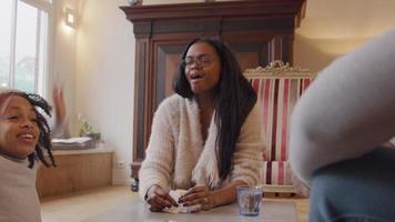 duas mulheres, um homem e uma menina sentados ao redor da mesa, jogando cartas. garota vence e fica feliz. mulher dá mais cinco à menina. video