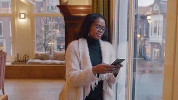 kvinnan står bredvid fönstret, ögonen på mobiltelefonen, smsar, ler. video