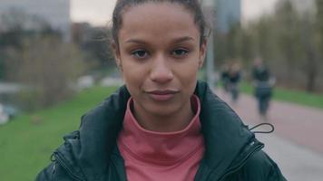 close-up de jovem negra, cabeça baixa, do lado de fora, coloca máscara e vai embora video