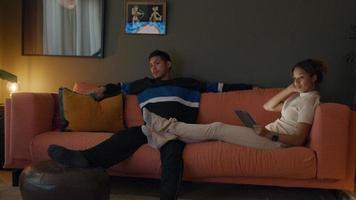 svart ung kvinna och ung man sitter på soffan och tittar på tv. video