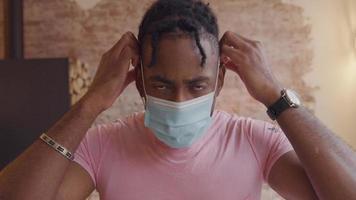 mannen vänder huvudet ner, tar på sig ansiktsmask medan han tittar in i kameran, justerar masken och lämnar video